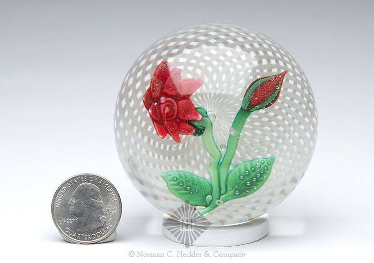 Antique New England Glass Company Flower And Bud Paperweight, New England Glass Company, Cambridge, Massachusetts, 1852-1888. Cylindrical with slightly concave base, red and green flower on white latticinio background, colorless ground, polished pontil scar, dia. 2 5/8 inches, ht. 1 7/8 inches; (light wear marks and blemishes). A simple flower with bud featuring New England Glass Company's latticinio background. Generally fine condition. Property of The Strong, sold to benefit the museum's…