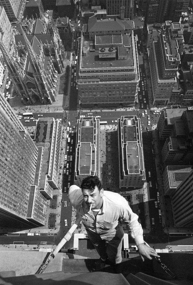 Window cleaner clings to the side of one of the skyscrapers in the Rockefeller Centre, protected by a safety harness. New York, 1950s (by William Lovelace). Person at Work photograph- The man in the photograph is very high up. He must of been doing this job for quite some time as he looks relaxed whilst smoking a cigarette. The composition of this photo gives a great depth of field.