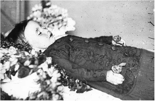 "Post Mortem but not wearing a ""death mask"". Where do people get these ideas??? Original label: This child is wearing a death-mask to cover the effects of decomposition that begin so quickly after death."