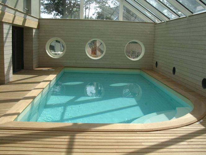 Piscine intérieure avec escalier d'angle arrondi, plages de bois clair et fenêtres hublots© L'Esprit Piscine