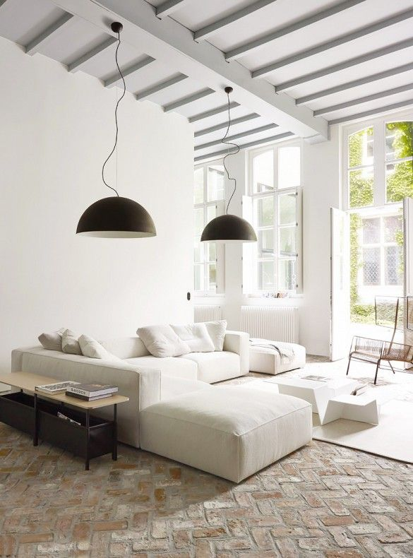 Large white sectional sofa in this cozy living room, along with brick flooring, black pendant lighting, and exposed ceiling beams.