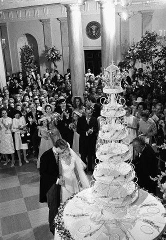 Tricia Nixon, figlia del presidente Nixon, taglia la torta nuziale con il marito Edward Finch Cox durante il ricevimento alla Casa Bianca, 1971. Il loro fu il primo matrimonio celebrato alla Casa Bianca. La torta a sei piani fu creata da Heinz Bender, il capo pasticcere della Casa Bianca, e decorata con fiorentini di zucchero rosa che portava le iniziali P e E a decoro della torta.