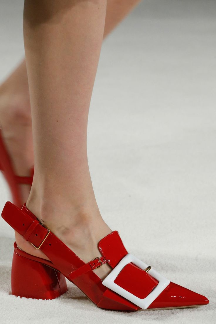 Fall '15 Accessories Trend Report   Into The Red   Miu Miu Red Patent Leather Slingbacks Have Extremely Pointy Toes and Block Heels with a Slight Curve in Them. Cutouts on Either Side of The Tongue Make It Possible to Add All Those Buckles, Including The Huge Decorative White One.