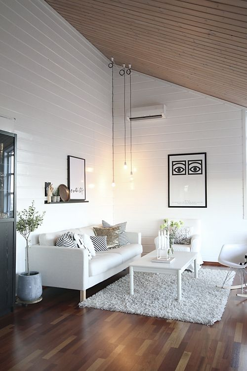 Love the grouping of hanging ceiling lights | White painted wood + natural Wood family room with sloped ceiling