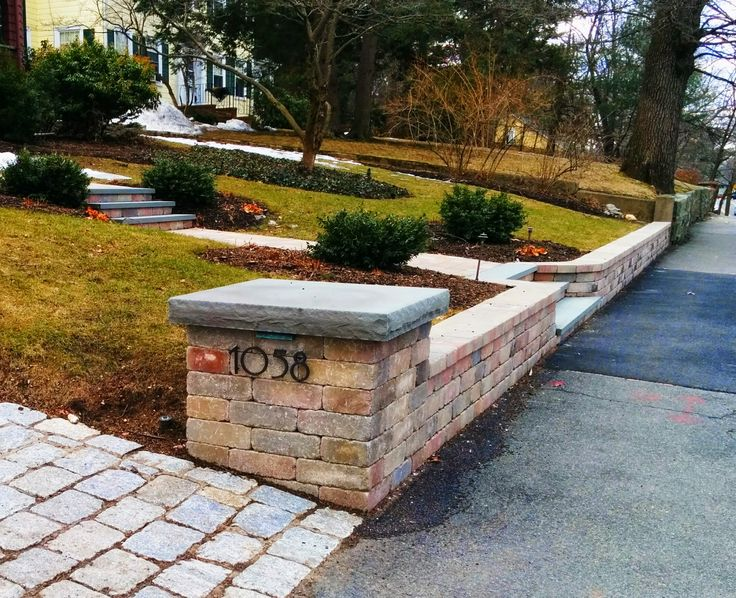 segmental concrete block retaining wall pillars and steps with bluestone accents built
