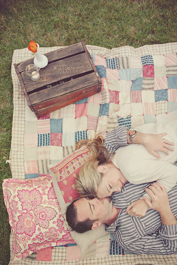 heart love weddings--couple cuddling on a pastel color block quilt, spring picnic engagement