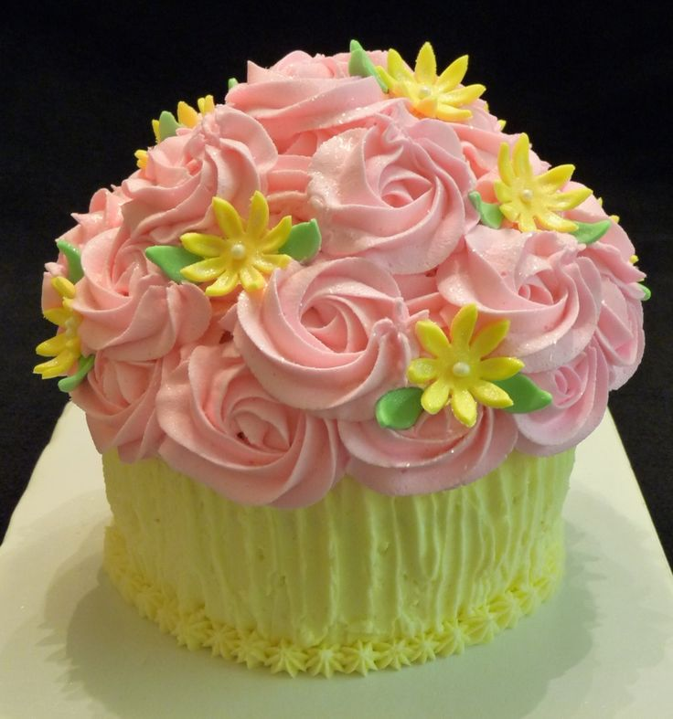 Giant cupcake using Wiltons cupcake pan. I used a spatula to create the lines in the frosting on the bottom. The top is done in 1M rosettes with fondant daisies and sprinkled with edible glitter. The cake is all buttercream frosting, lemon cake torted with a raspberry filling.