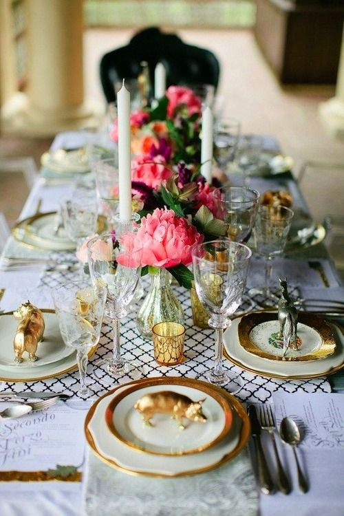 Layered place settings with gold rims and gold  silver animal figures on plates.