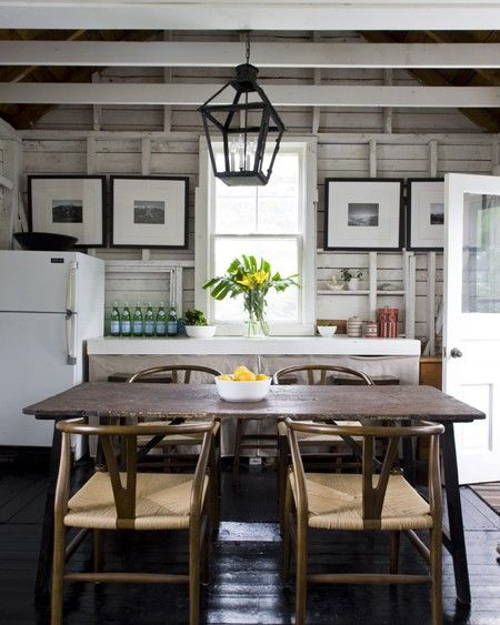 Opt for an intentionally unfinished look.    Exposed rustic planks and beams give this cottage kitchen a dramatic sense of height. The darker wood farm table and chairs break up the monochromatic palette. The undone vibe of the kitchen, complete with linen curtains covering lower shelves instead of closed cabinets, offers even more character.