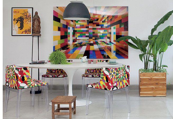 A sala de jantar colorida tem quadro do fotógrafo Valentino Fialdini, cadeira Mademoiselle, mesa Saarinen e até a imagem de uma santa.