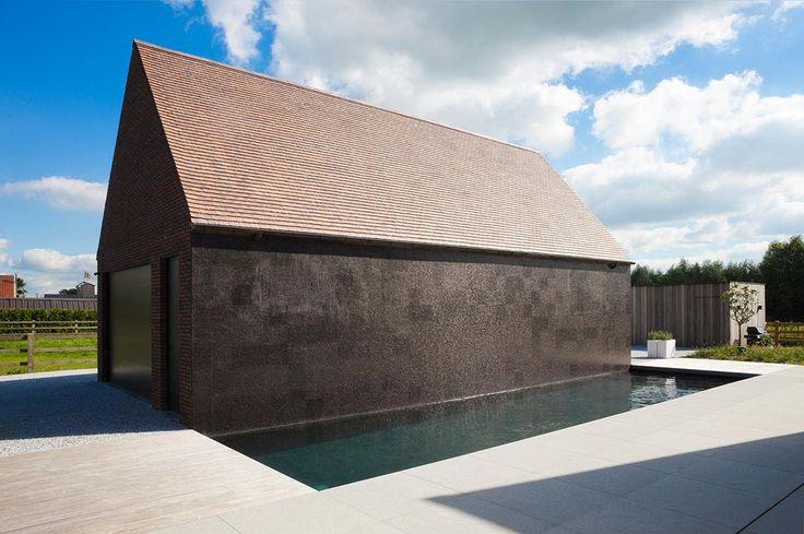 Betonnen zwembad op de binnenplaats van een prachtig verbouwde hoeve