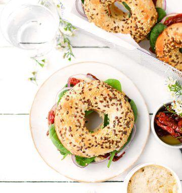 Bagel houmous, pousses d'épinards, tomates séchées et oignon rouge : photo de la recette