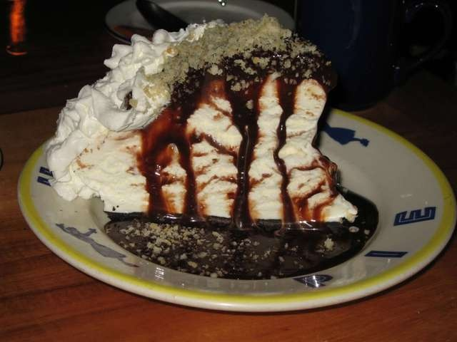 """Kimo's famous """"Hula Pie"""" (Front Street, Lahaina)  1 (9-inch size) chocolate cookie crumb crust  1 quart macadamia nut ice cream, softened  1 jar (12 ounce size) hot fudge ice cream topping  1 container (8 ounce size) Cool Whip  1 jar (3 ounce size) macadamia nuts, chopped    Fill pie crust with ice cream and re-freeze until firm.     To serve, top with fudge, cool whip and sprinkle with nuts"""