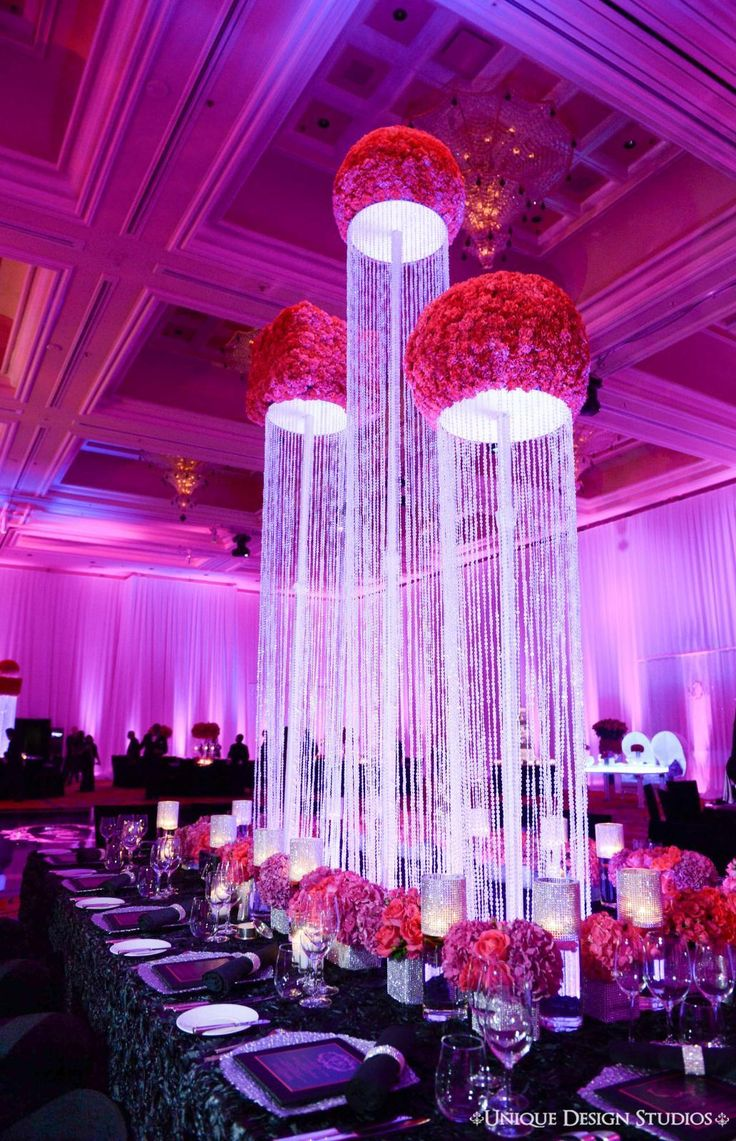 Stunning Crystal Waterfall and Rose Centerpieces Stunning Crystal Waterfall and Rose Centerpieces fuchsia rose ballroom chandeliers crystals centerpieces dining tables lighting linens table setting Tiffany Cook Events Tiffany Cook Events Encore Hotel Florist Tiffany Cook Events Unique Design Studios Tiffany Cook Events Tiffany Cook Events Encore at Wynn-Las Vegas