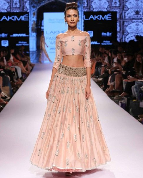 Payal Singhal Blush pink off shoulder crop top with zardozi embroidered floral motifs. Full sleeves. Matching Lehenga featuring zardozi embroidery in floral accents with cut work belt at waist line. Disclaimer: There might be a slight color variation in this item as this image is from the actual runway show.Wash Care: Dry clean only