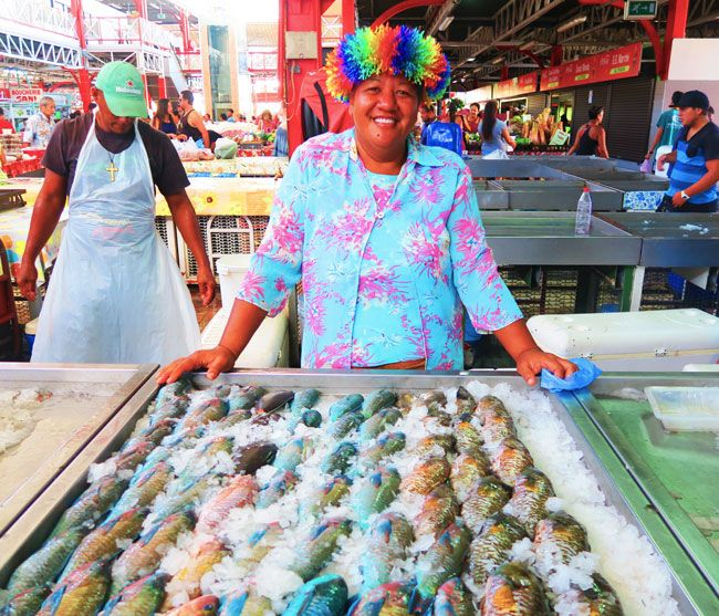 A friendly local selling freshly caught fish at the Papeete Market in Tahiti