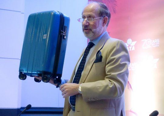 International Air Transport Association (IATA) senior vice president for airport, passenger, cargo and security, Tom Windmuller, holds up the group's proposed ideal-sized carry on bag, on June 9, 2015