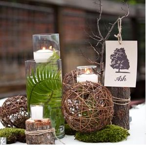 wood pieces, rocks, brown wicker balls, fresh green moss, curly willow tips, seeded eucalyptus, and submerged maidenhair fern in a cylinder vase with a floating candle on top.