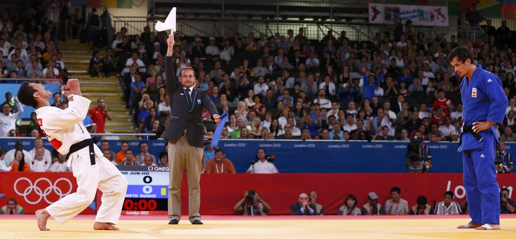 Winner and loser - South Korean Cho Jun-Ho celebrates after defeating Spanish Sugoi Uriarte in a bronze medal judo match at the 2012 London Olympic Games.