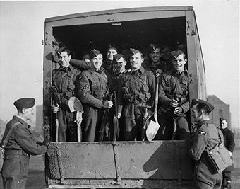 Recruits to the newly-formed RAF Regiment for aerodrome defence in the back of a lorry taking them to an airfield. Officers are drawn from the Army and RAF. At first they wore khaki battledress with RAF insignia later RAF uniforms were provided.