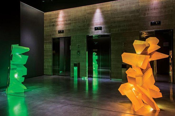 Frente a los ascensores del primer piso del hotel Nhow Milano, esculturas transiluminadas en color verde y naranja.