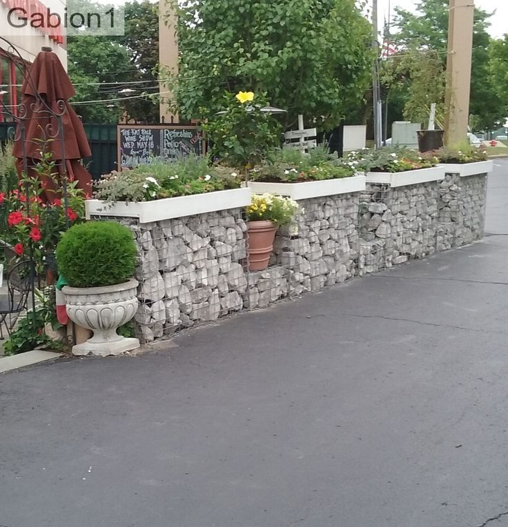 gabions with small garden planters capping them https://www.gabion1.com