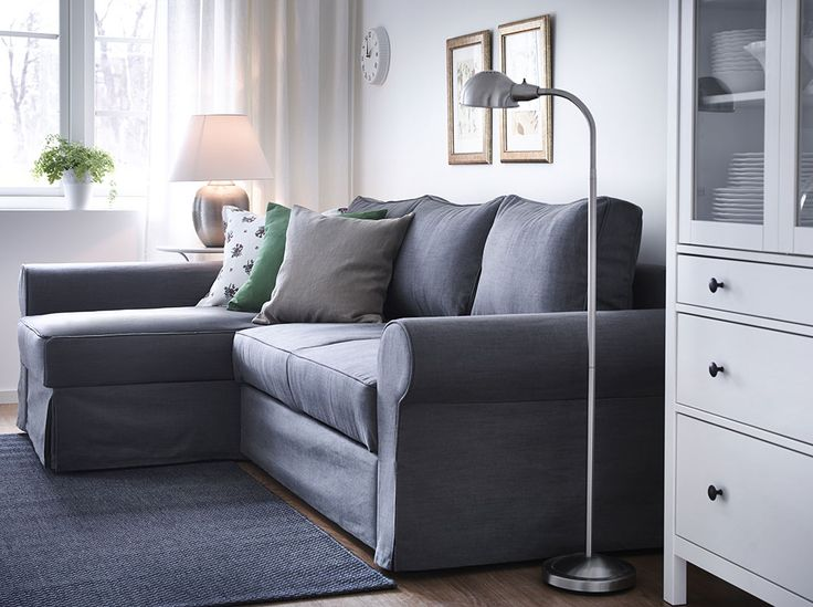 A living room with a three-seat sofa-bed with a chaise longue and a grey cover