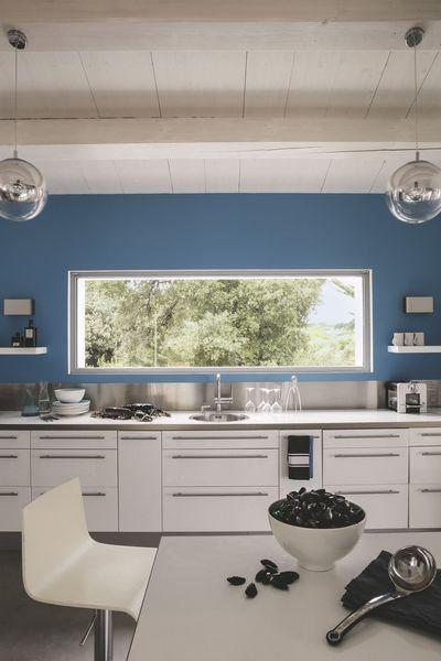 Grâce à sa large baie horizontale, la spacieuse cuisine, fonctionnelle et lumineuse, donne le sentiment d'être en pleine nature. Le bleu royal électrise la cuisine qui s'efface derrière le blanc omniprésent. Cuisine, Ikea ; suspensions en verre, Castorama ; sol en béton ciré gris