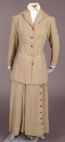Tan linen suit with divided skirt (for bicycling or riding), American, c. 1909-1915. The tailored suit has a long jacket with four buttons in front, and two buttons on the cuff of each sleeve. The skirt has eleven buttons on the panel that conceals the pants, and a separate belt. Note: Helen Andrus Merrell Howard, daughter of Dr. Frank D. Howard, married Francis (C.or E.) Merrell c. 1908, and moved to Las Cruces, New Mexico.