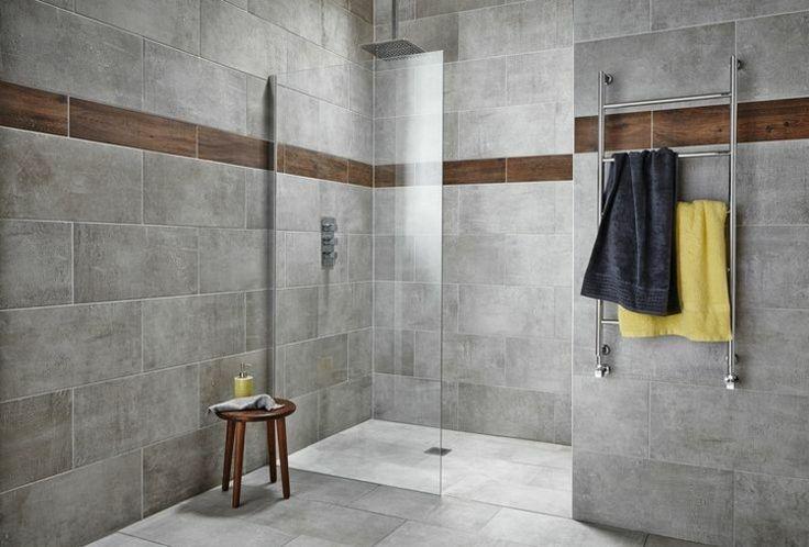 salle de bains avec carrelage gris mural et de sol avec frise marron, douche italienne avec parois en verre et tabouret en bois