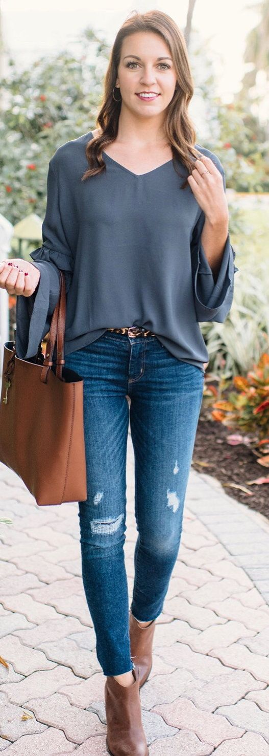 #spring #outfits woman wearing black v-neck long-sleeve shirt , distressed denim jeans and carrying brown leather tote bag. Pic by @absolutelyanniee