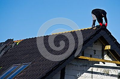 Detail of the roof under construction with black rooftiles unfinished and roofer on top working.