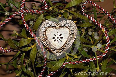 Gold heart on a background of mistletoe