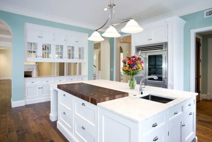 Vibrant light blue and white dominates this kitchen featuring bright cabinetry over natural hardwood flooring. Island features built in sink and cutting board space.