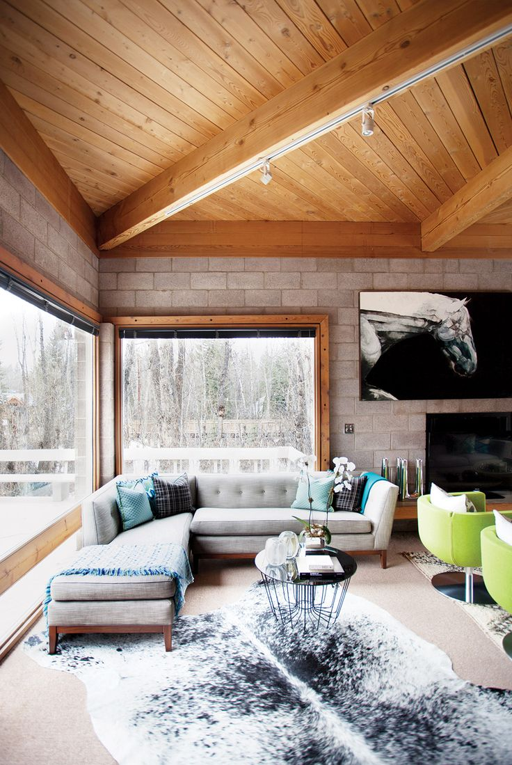 love the couch - that is the idea i want so that you can see-through the window and be part of the room too   - Reading nook in living room with L-shaped sofa, blue pillows, and cowhide rug