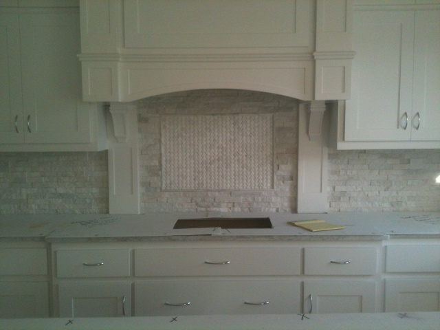 carrera marble countertops and white carrera ledger stone backsplash