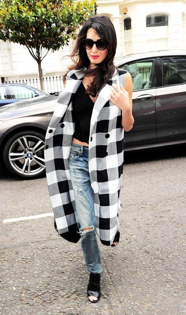 Amal Clooney wears a black tank top, distressed jeans, a long checked vest, and peep-toe booties