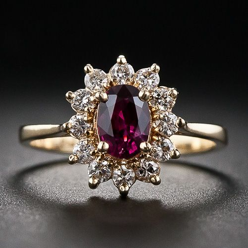 This is a small-scale traditional cluster ring featuring a sweet .60 carat ruby. The faceted oval-cut ruby is wrapped with a sparkling diamo...