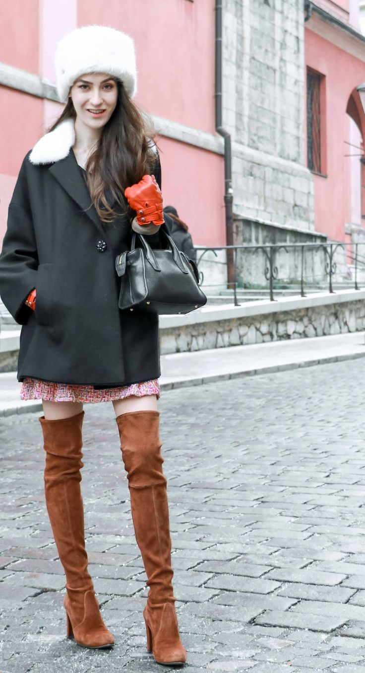 Fashion Blogger Veronika Lipar of Brunette from Wall Street dressed in faux fur hat, black and white Escape short coat, mini velvet skirt from Storets, brown Stuart Weitzman over the knee boots, brunt orange leather gloves for an outdoor party