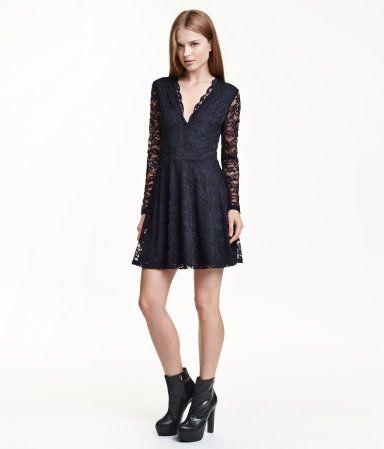 Kurzes Spitzenkleid mit Tellerrock und langem Arm. Das Kleid hat einen tiefen V-Ausschnitt mit Wellenkante und ein eingenähtes, figurnahes Unterkleid aus Jersey.