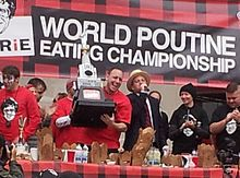Joey Chestnut lifts the trophy at the 2012 World Poutine Eating Championship in Toronto, Ontario
