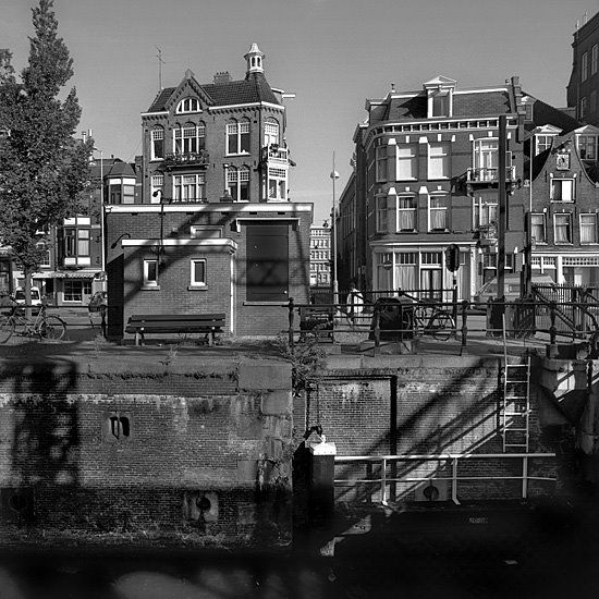Scharrebiersluis in Amsterdam. The cast iron drawbridge (behind it is a pound lock named Rapenburgersluis) was built over the Schippersgracht in 1906 by the Nederlandsche Fabriek van Werktuigen en Spoorwegmateriaal Amsterdam (later in 1929 the name was changed to Werkspoor N.V.). The electrical unit dates from 1911. It still functions for traffic over water and over land. #amsterdam #historicsites #Scharrebiersluis