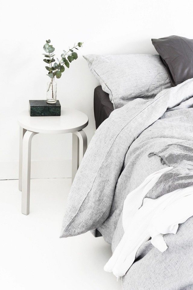 Swedish bedroom with gray bedding and an IKEA stool doubling as a nightstand