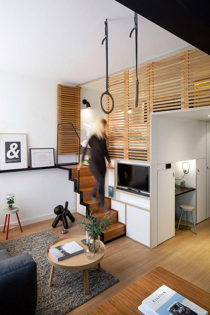 Un studio avec mezzanine derrière des panneaux de bois ajourés
