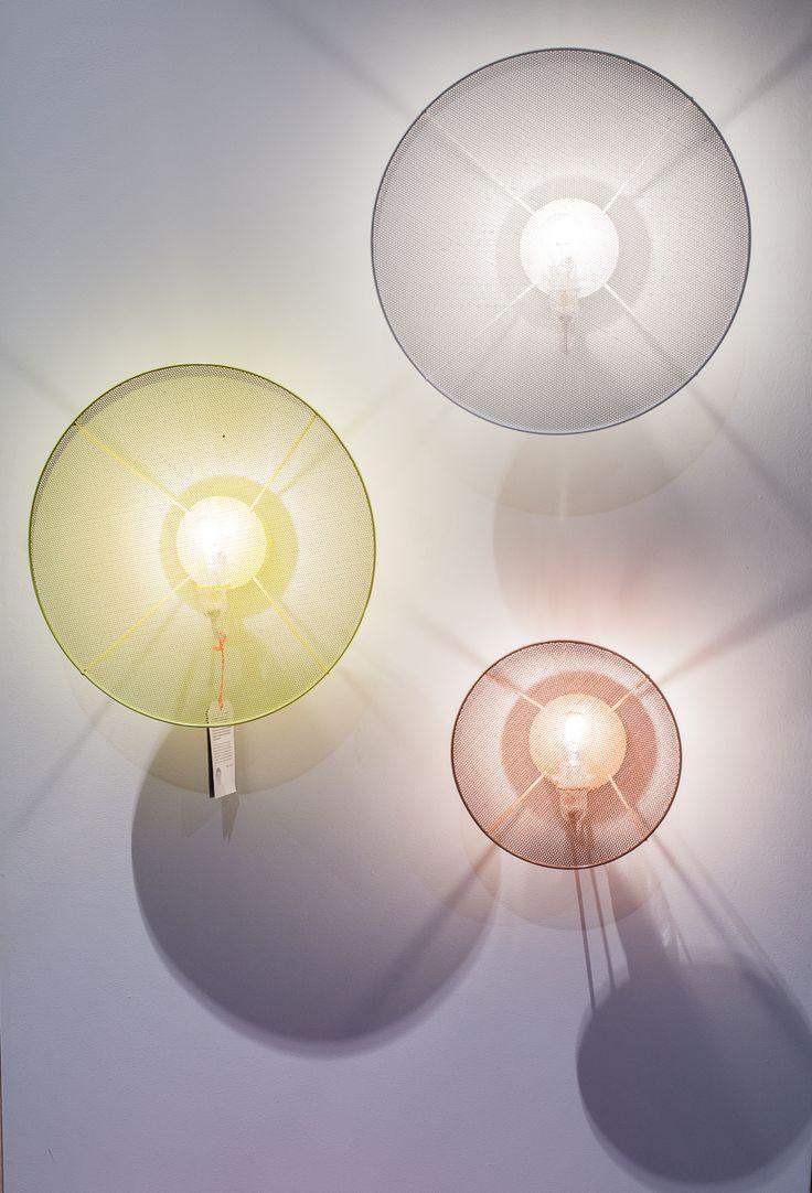 Mis au point par la designer Elise Fouin, ce luminaire met en avant de manière très simple et élégante l'ampoule. Le revêtement ne fait finalement qu'habiller la source lumineuse de manière discrète. Ce disque de métal perforé laisse passer abondamment la lumière.