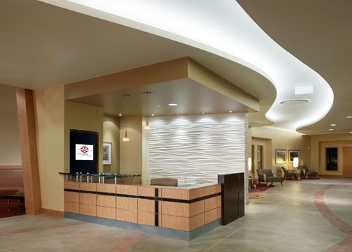 The main lobby of the clinic space leads to the Lab, Urgent Care, Diagnostic Imaging, the Healthy Living Resource Center, and Radiation Oncology. Wind is expressed in the sculptured wall behind the welcome desk and in the textures and sinuous curves that flow through the ceiling. The lobby also has a café.