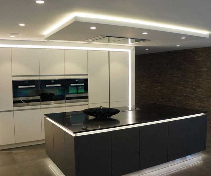 A monochromatic modern kitchen with lighting around the perimeter in addition to the small pot lights in the ceiling. To the right is a stacked stone wall.