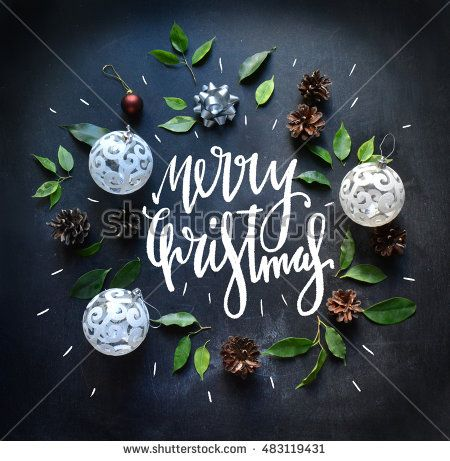 Merry Christmas Background. Leaves, balls and hand written letters on blackboard. Hipsters Merry Christmas background. Flat lay, top view. Trendy lettering. Merry Christmas and Happy New Year 2017