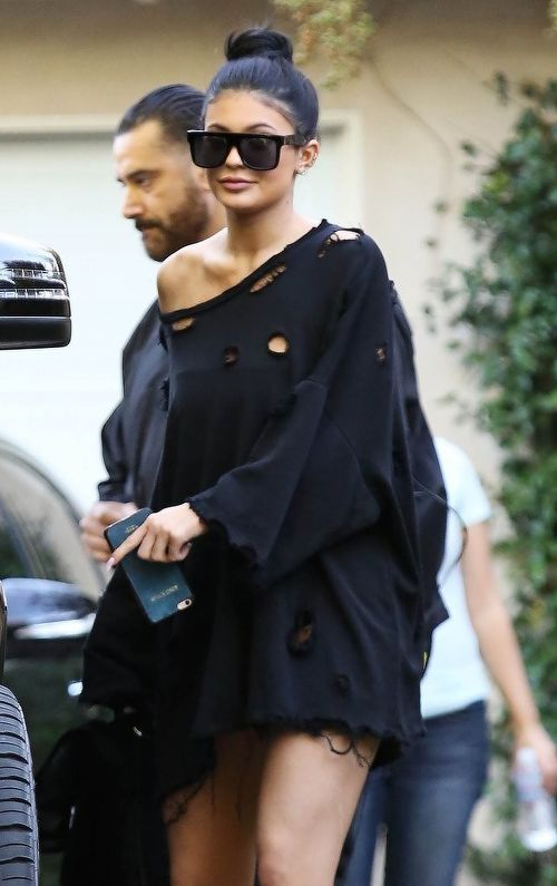 Kylie Jenner StreetStyle: ripped baggy sweat shirt + dark glasses + high bun