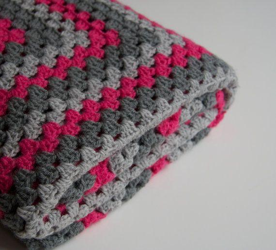 Handgemaakte granny square deken. Hij bevat de kleuren roze, lichtgrijs en donkergrijs. De deken is 110 x 110 cm. Ideaal om als deken op de bank